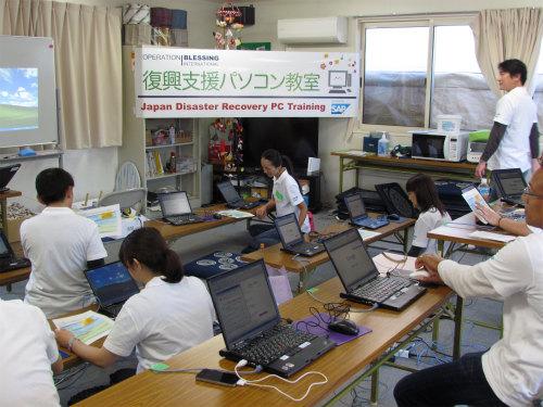 手早くセッティングを行うSAP Japan TEARS team(SAPジャパン株式社の震災復興支援チーム)の皆さん。 今回の教室で使用しているノートパソコン20台は、Japan TEARSから寄贈されたものです。