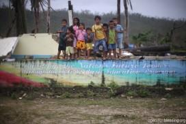 パグナミタン村の子供たち。塀には「幼稚園から高校までの教育が国の将来のリーダーを育てる」と書かれています。
